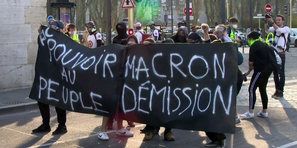 Des manifestants en noir, derrière une banderole, à 50 mètres des gendarmes mobiles / Copyright Emma Audrey / Radio BIP / Média 25